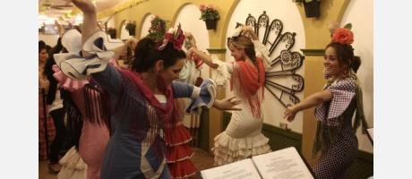 Sevillanas bailando dentro de una de las casetas del reciento ferial