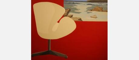 Cuadro en fondo rojo que muestra una silla frente a una pintura del mar