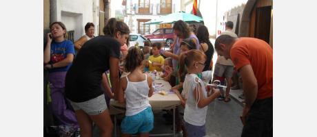 Un grupo de niños realizan actividades en torno a una mesa asesorados por los m