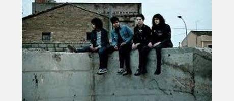 jóvenes sentados en el muro de una terraza