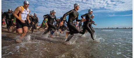 imagen de atletas corriendo por la orilla de la playa